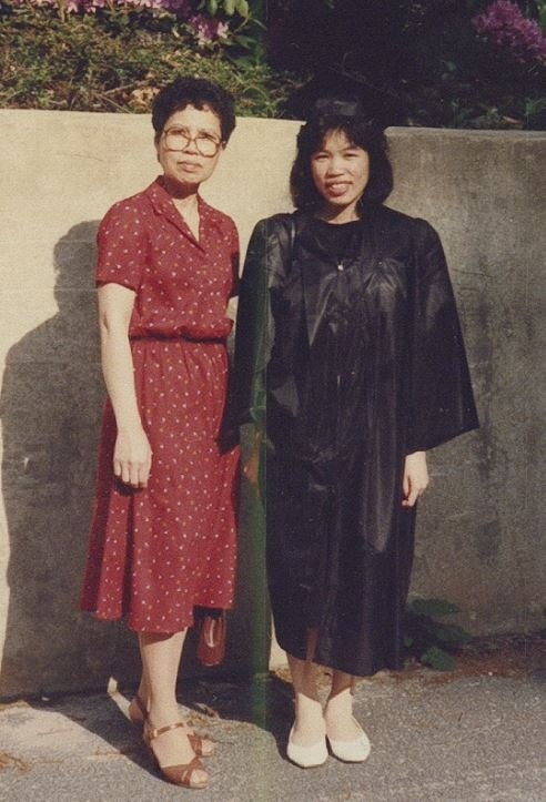 Mrs. Wong stands with her daughter Alison in a graduation robe.